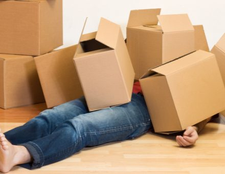 Sick or tired man laying face-up under a pile of cardboard moving boxes in an unfurnished room