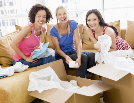 Three girl friends unpacking boxes in new home smiling